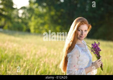 5. Juni 2010 - 5. Juni 2010 - lange rote Haare Frau im romantischen Sonnenuntergang Wiese mit Blumenstrauß - Stockfoto