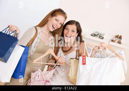 5. Juni 2010 - 5. Juni 2010 - Fashion einkaufen - zwei glückliche junge Frau wählen Sie Kleidung im Shop hält Einkaufstasche - Stockfoto