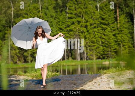 5. Juni 2010 - 5. Juni 2010 - Happy romantische Frau mit Sonnenschirm in der Sonne, weißen Kleid, zu Fuß in Wasser - Stockfoto