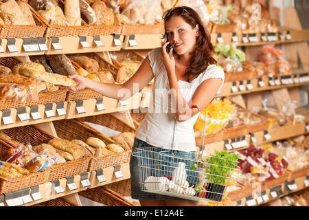 15. Mai 2009 - 15. Mai 2009 - Lebensmittelgeschäft: junge Frau halten Handys und Warenkorb Ã'Â © CTK/ZUMAPR - Stockfoto