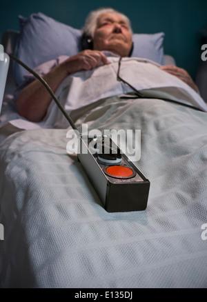 Notruftaste Pflege ältere Dame mit Kopfhörern in der stationären Versorgung Bett nachts mit Notruftaste an ihre - Stockfoto
