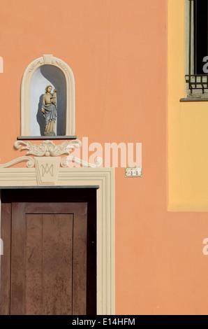 Orangefarbenen Fassade des kleinen Kapelle mit religiösen Statue in der Nische Altstadt Menton Alpes-Maritimes Frankreich - Stockfoto