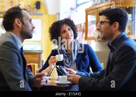 Die Menschen bei Bar mit Team Kollegen treffen in der Cafeteria, arbeiten mit dem Ipad und Kaffee trinken - Stockfoto