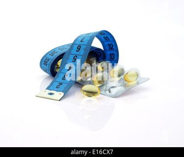 Nahrungsergänzungsmittel zur Gewichtsreduktion. Maßband und Medikamente auf weißem Hintergrund - Stockfoto