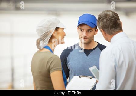 Supervisor und Arbeitnehmer sprechen in Lebensmittel verarbeitenden Anlage - Stockfoto