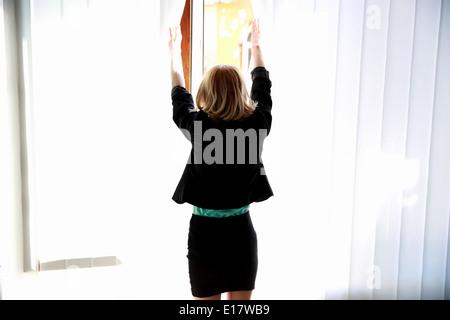 Rückansicht-Porträt einer jungen Frau am Fenster suchen - Stockfoto