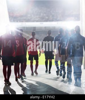Silhouette der Fußballer zu Fuß zum Feld - Stockfoto