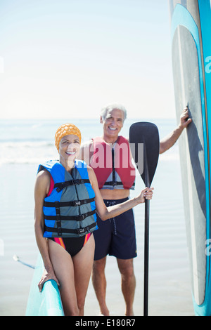 Porträt von älteres Paar mit Paddleboards am Strand - Stockfoto