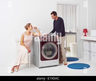 Hausarbeit, junge Frau und Mann, die Wäsche zu Hause - Stockfoto