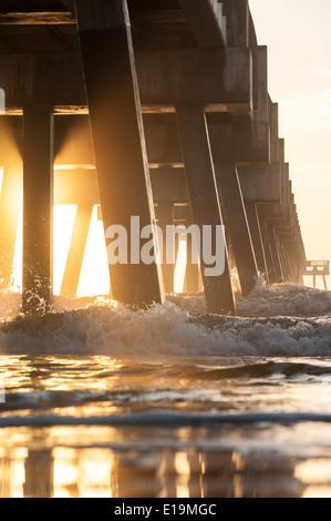 Die aufgehende Sonne beleuchtet einen am frühen Morgennebel unter der Jacksonville Beach Pier im Nordosten Florida/USA. - Stockfoto