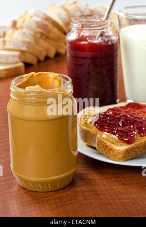 Peanut Butter und Gelee-Flaschen mit Brot und ein Glas Milch. - Stockfoto