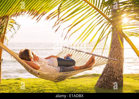 Romantisch zu zweit entspannen in tropical Hängematte bei Sonnenuntergang - Stockfoto