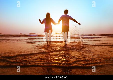 junge Brautpaar laufen ins Meer bei Sonnenuntergang Strand
