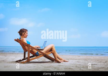 Frau im Bikini am Strand sitzen mit laptop - Stockfoto
