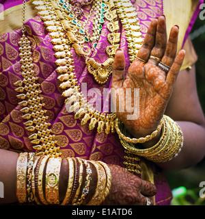 Die Hände eines indischen Braut geschmückt mit Schmuck, Armreifen und mit Henna bemalt - Stockfoto