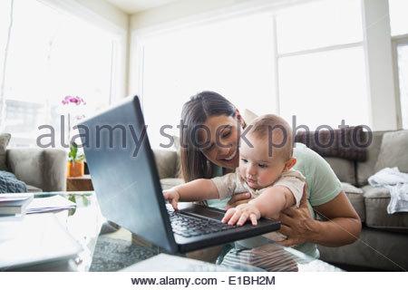 Mutter und Baby mit Laptop im Wohnzimmer - Stockfoto
