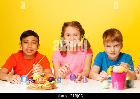 Zwei jungen und Mädchen malen Ostereier am Tisch - Stockfoto