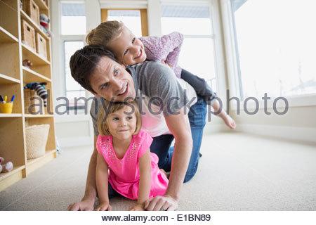 Vater und Töchter spielen im Wohnzimmer - Stockfoto