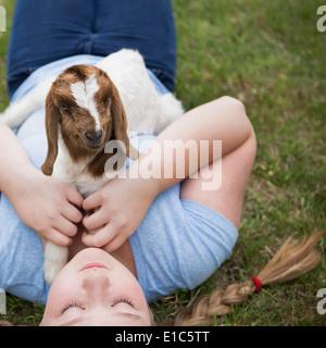 Ein Mädchen kuscheln eine Baby-Ziege liegend auf der Brust. - Stockfoto