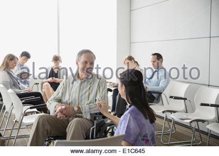 Krankenschwester im Gespräch mit älteren Patienten im Rollstuhl - Stockfoto