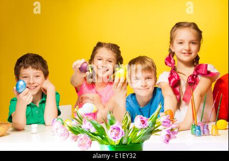 Vier Kinder mit bunten Ostereiern - Stockfoto