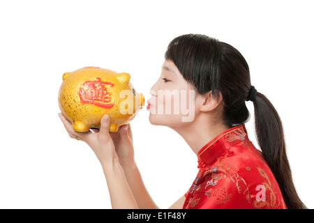 Schöne chinesische Frau trägt ein traditionelle Kleid bekannt als ein Chipao hält ein Sparschwein - Stockfoto