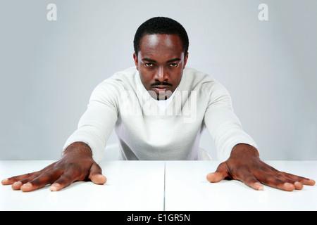 Ernsthafte afrikanischen Mann am Tisch sitzen, auf grauem Hintergrund - Stockfoto