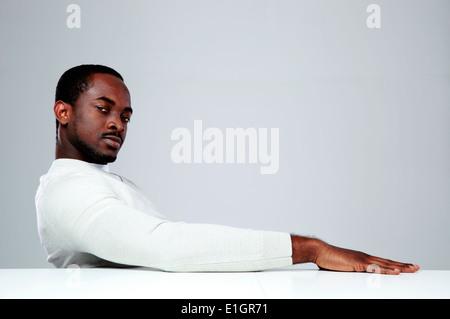 Nachdenklicher afrikanischen Mann am Tisch sitzen, auf grauem Hintergrund - Stockfoto