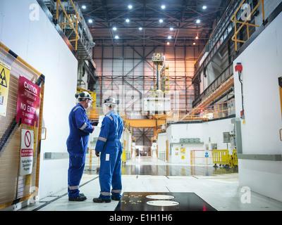 Ingenieure in der Diskussion in der Reaktorhalle im Kernkraftwerk - Stockfoto