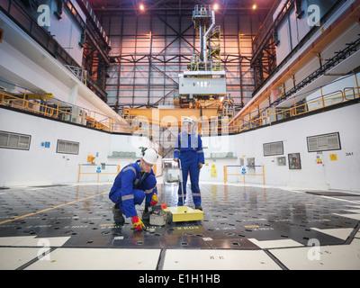 Ingenieure mit Sensoren am Pfahlkopf im Kernkraftwerk - Stockfoto