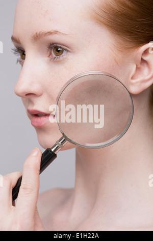 Porträt der jungen Frau, die Lupe auf Wange - Stockfoto