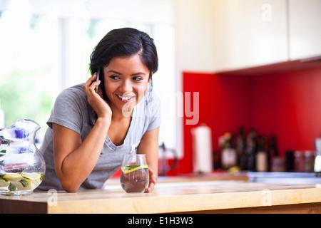 Junge Frau mit Handy in Küche - Stockfoto