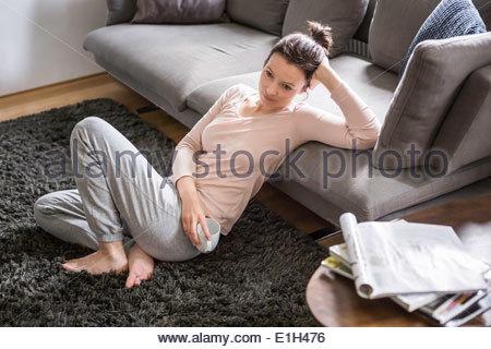 Mitte Erwachsene Frau sitzen auf Teppich mit Kaffee - Stockfoto