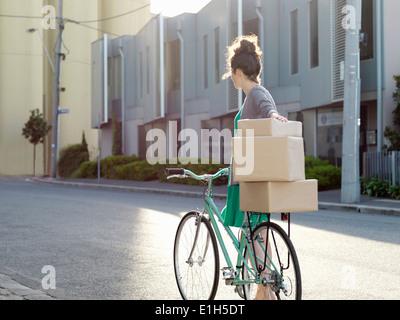 Junge Frau schob Fahrrad mit Kartons - Stockfoto
