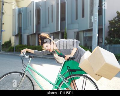 Junge Frau mit dem Fahrrad und fallende Kartons - Stockfoto