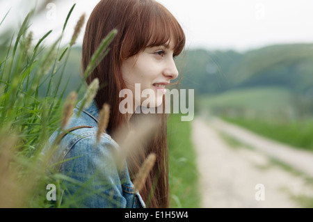 Porträt der jungen Frau neben Feldweg - Stockfoto