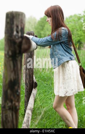 Junge Frau stützte sich auf Holzzaun - Stockfoto