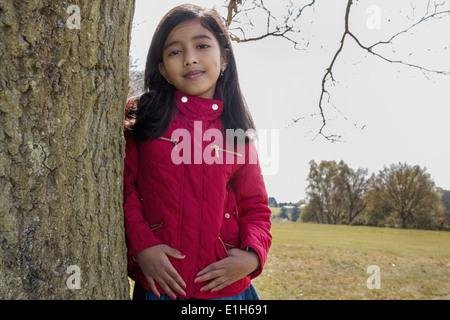 Porträt eines Mädchens Baumstamm gelehnt - Stockfoto