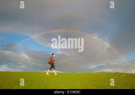 Junge weibliche Wanderer, Wandern unter Regenbogen - Stockfoto
