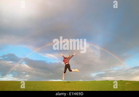 Junge weibliche Wanderer springen Luft unter Regenbogen - Stockfoto