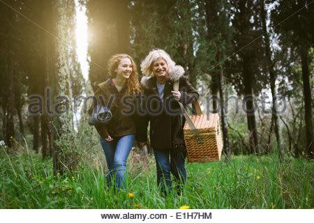 Mutter und Tochter im Teenageralter ein Spaziergang mit Picknick-Korb - Stockfoto