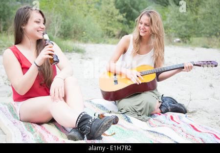 Freunde sitzen in Feld, Gitarre spielen - Stockfoto