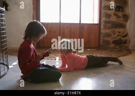 Bruder und Schwester im Wohnzimmer spielen - Stockfoto