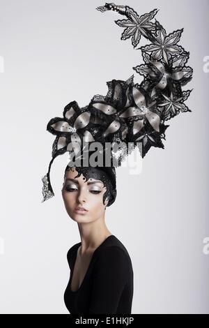 Fantasie. Surrealismus. Erstaunliche Frau in trendige Kopfbedeckung mit Blumen - Stockfoto
