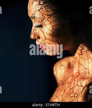 Art Deco. Ethnische Frau Gesicht mit Reflex aus durchbrochener Spitze - Phantasie Make-up - Stockfoto