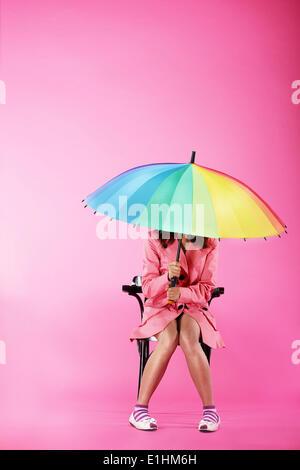 Vogue. Frau in rosa Mantel sitzend mit bunten Regenschirm - Stockfoto