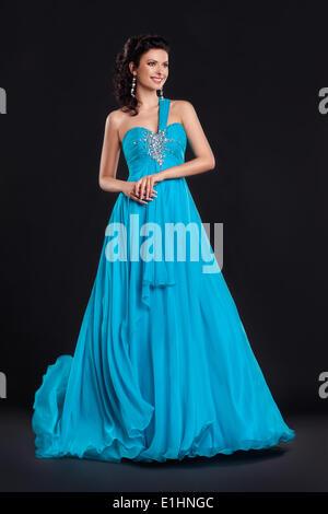 Porträt von trendigen jungen Frau im trendigen blauen Kleid, die lächelnd auf schwarzem Hintergrund Stockfoto
