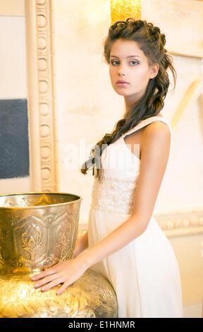 Luxuriöse schicke Brunette im weißen Kleid. Orientalische antike goldene Dekor - Stockfoto