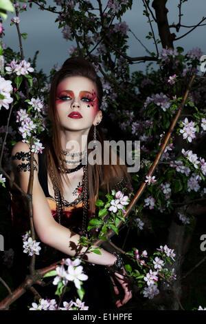 Junge schöne kreative Frau mit bunten Make up in blühenden Apfelgarten - Stockfoto