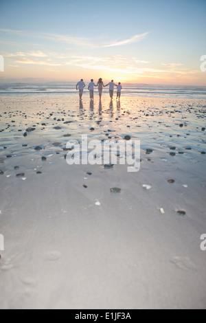 Familie läuft in Richtung Meer bei Sonnenuntergang, Cape Town, Südafrika - Stockfoto